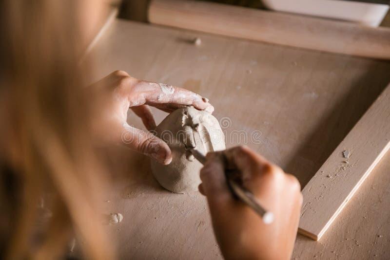 El niño pequeño esculpe de la arcilla con interés fotos de archivo