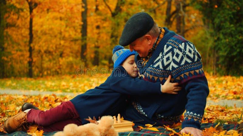 El niño pequeño está abrazando a su abuelo se está sentando en el parque del otoño imágenes de archivo libres de regalías