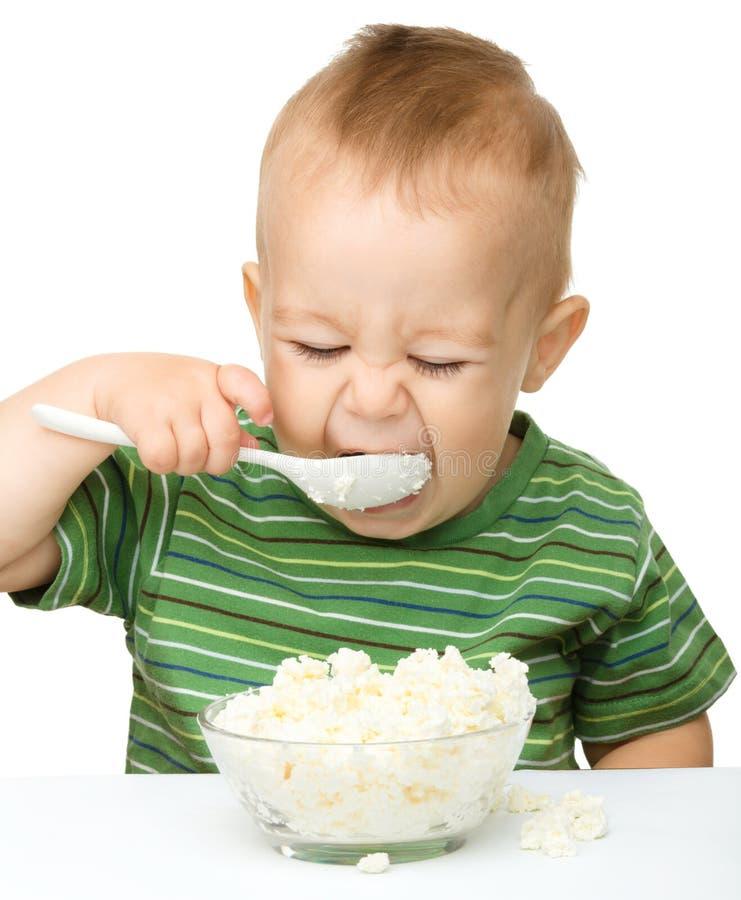 El niño pequeño está comiendo el requesón usando la cuchara fotos de archivo