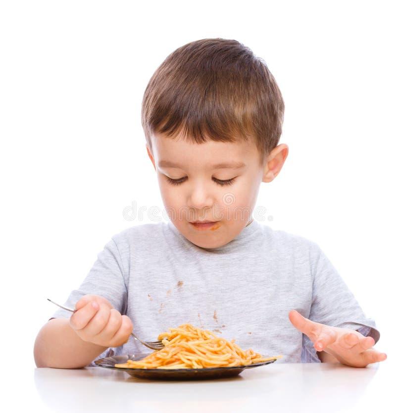 El niño pequeño está comiendo los espaguetis imagen de archivo libre de regalías