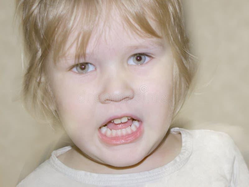 El niño pequeño está enojado, enojado, griterío, intentando golpear imagenes de archivo
