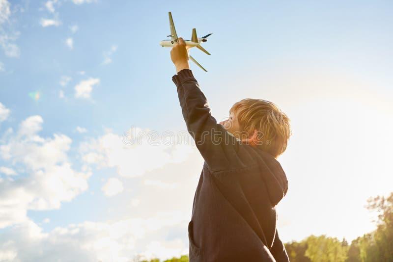 El niño pequeño está jugando con un aeroplano modelo foto de archivo libre de regalías