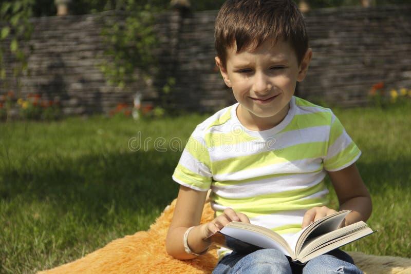 El niño pequeño está leyendo un libro en la hierba foto de archivo libre de regalías