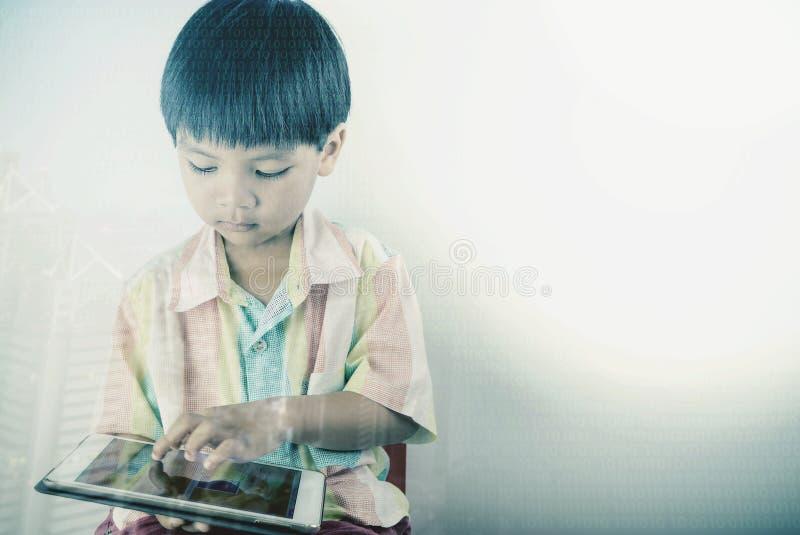 El niño pequeño está utilizando la tableta con la codificación y la educación digitales imagen de archivo libre de regalías
