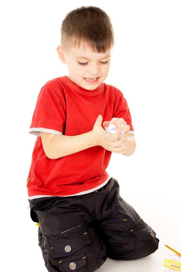 El niño pequeño estaba enojado y arruga la hoja de papel imagen de archivo libre de regalías
