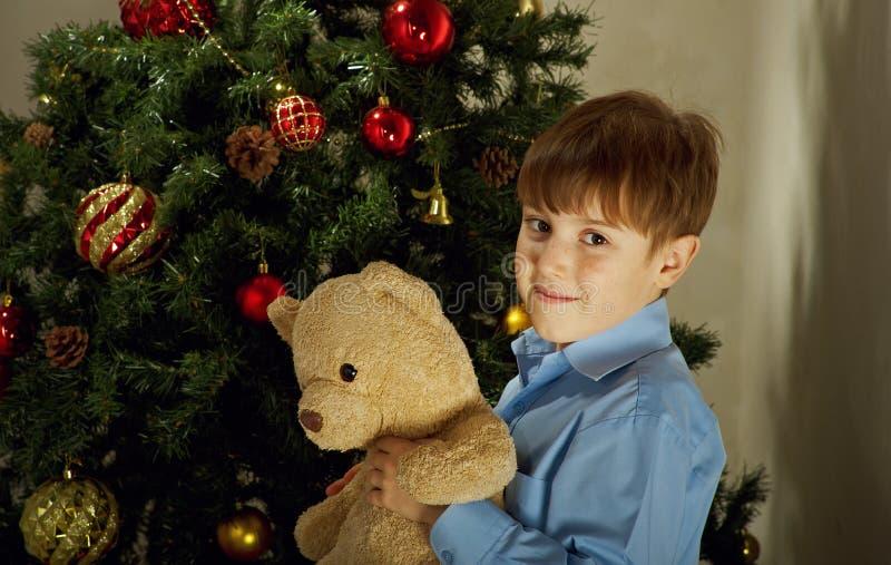 El niño pequeño feliz adorna el árbol de navidad i fotos de archivo