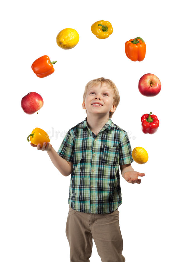 El niño pequeño hace juegos malabares algunas frutas y verduras fotos de archivo