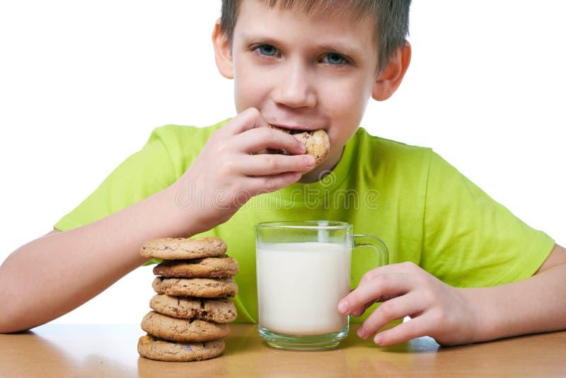 El niño pequeño hace las galletas y la leche del desayuno aislar imagen de archivo