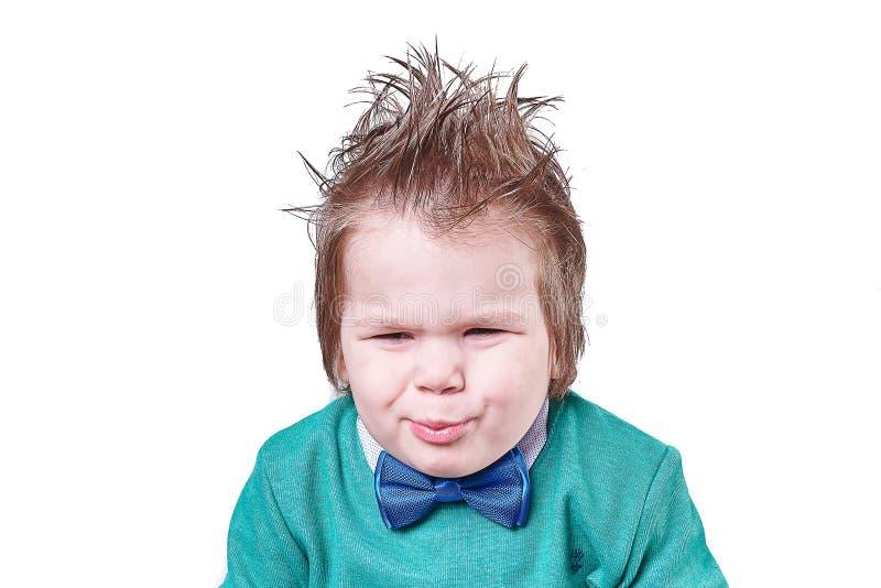 El niño pequeño hermoso en corbata de lazo azul y suéter verde, y ella hace las caras divertidas aisladas en el fondo blanco fotografía de archivo