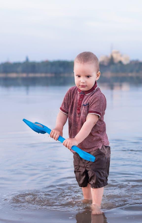 El niño pequeño juega con agua en el lago fotografía de archivo