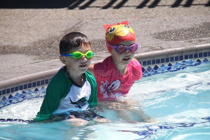 El niño pequeño/la muchacha hermana listo para nadar en piscina fotografía de archivo