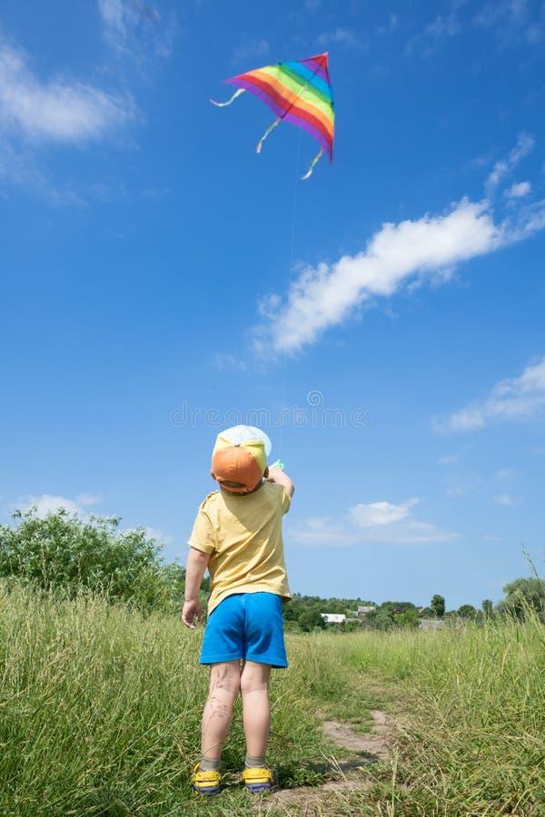 El niño pequeño lanza la cometa colorida en el cielo azul fotografía de archivo libre de regalías