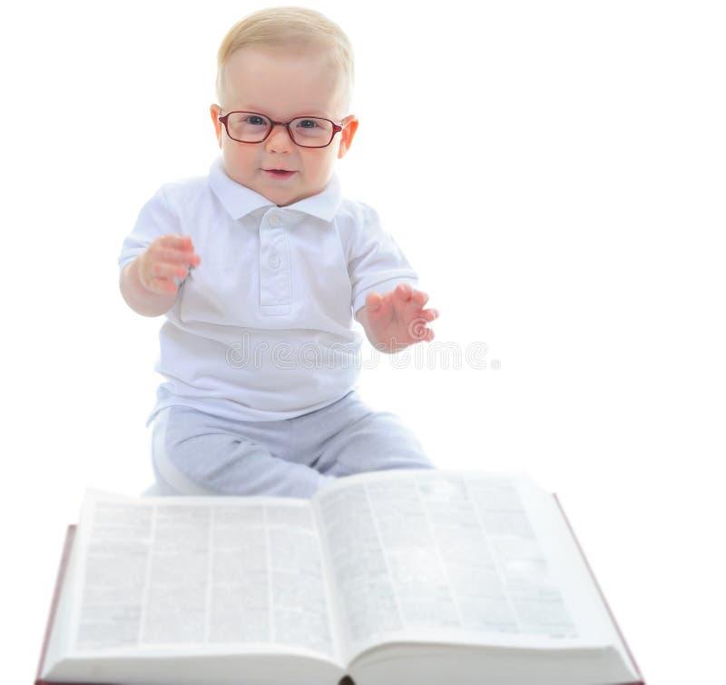 El niño pequeño lee un libro grande imágenes de archivo libres de regalías
