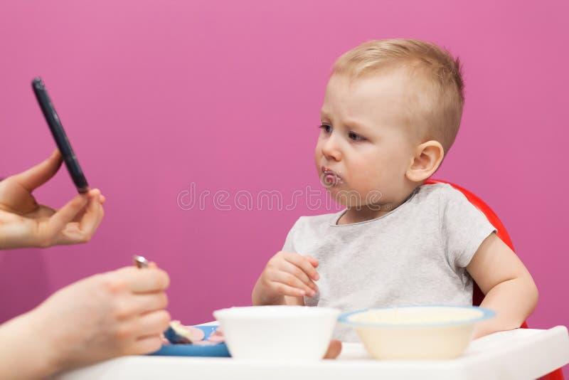 El niño pequeño lindo, come el desayuno en casa, mientras que mira la historieta en la tableta fotos de archivo