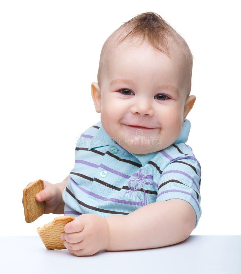 El niño pequeño lindo es galletas y sonrisa de la explotación agrícola foto de archivo libre de regalías