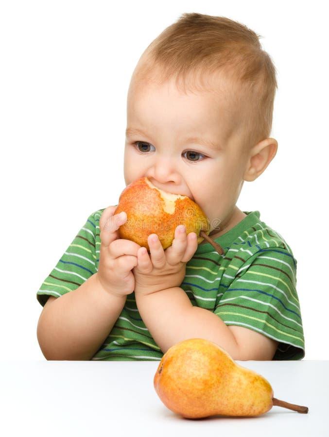 El niño pequeño lindo es pera penetrante foto de archivo