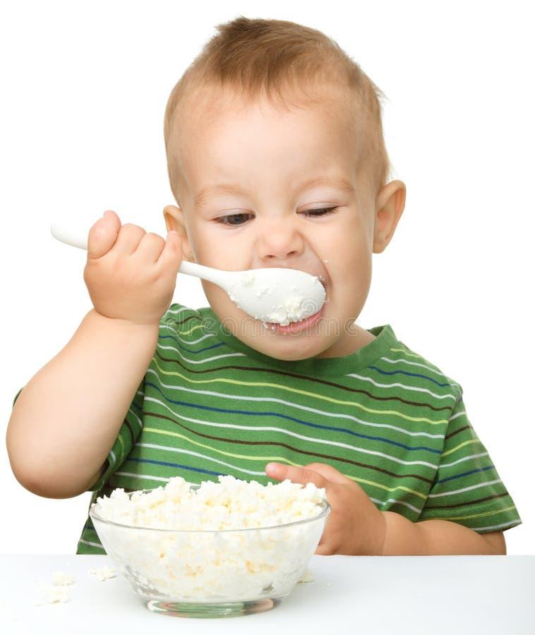El niño pequeño lindo está comiendo el requesón fotografía de archivo
