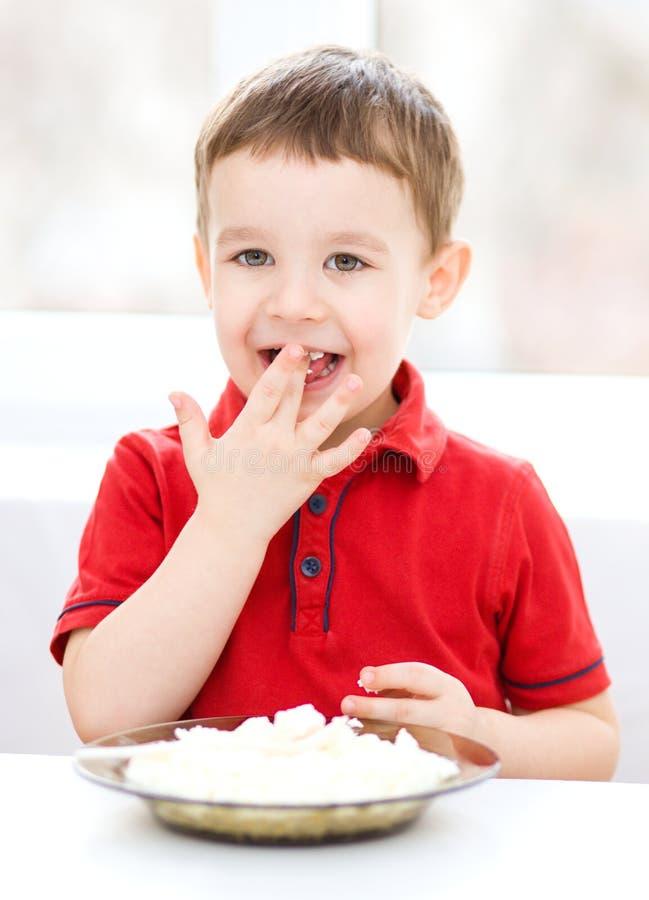 El niño pequeño lindo está comiendo el requesón imagen de archivo