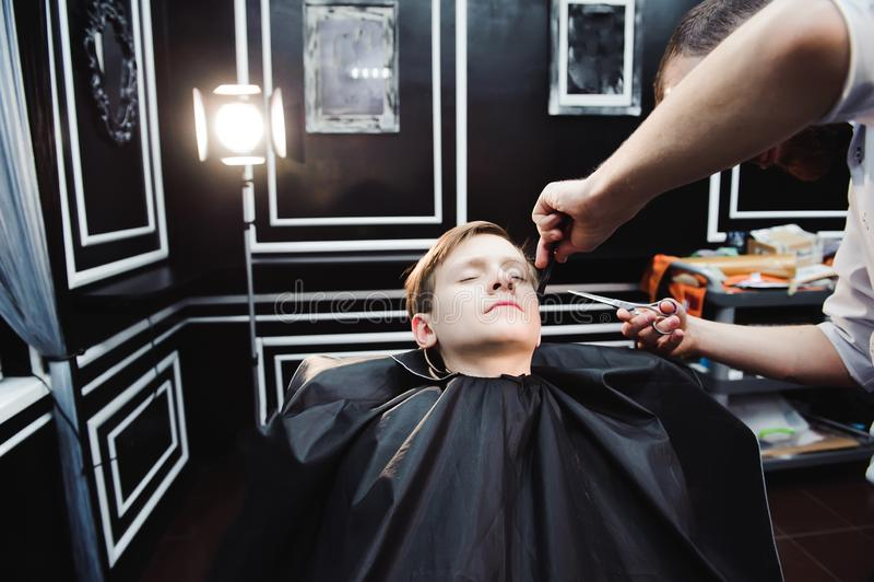 El niño pequeño lindo está consiguiendo corte de pelo del peluquero en la barbería fotos de archivo libres de regalías