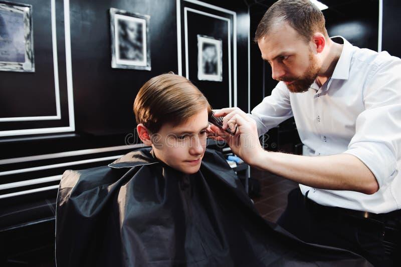 El niño pequeño lindo está consiguiendo corte de pelo del peluquero en la barbería fotos de archivo