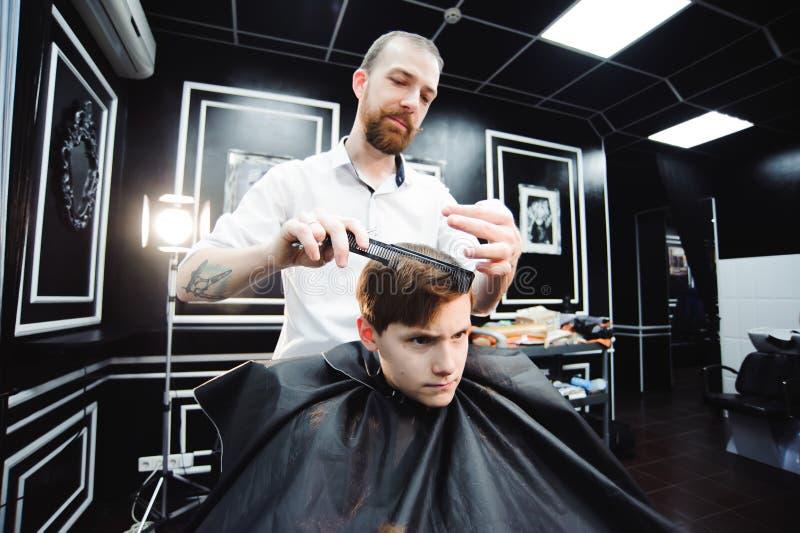 El niño pequeño lindo está consiguiendo corte de pelo del peluquero en la barbería fotografía de archivo