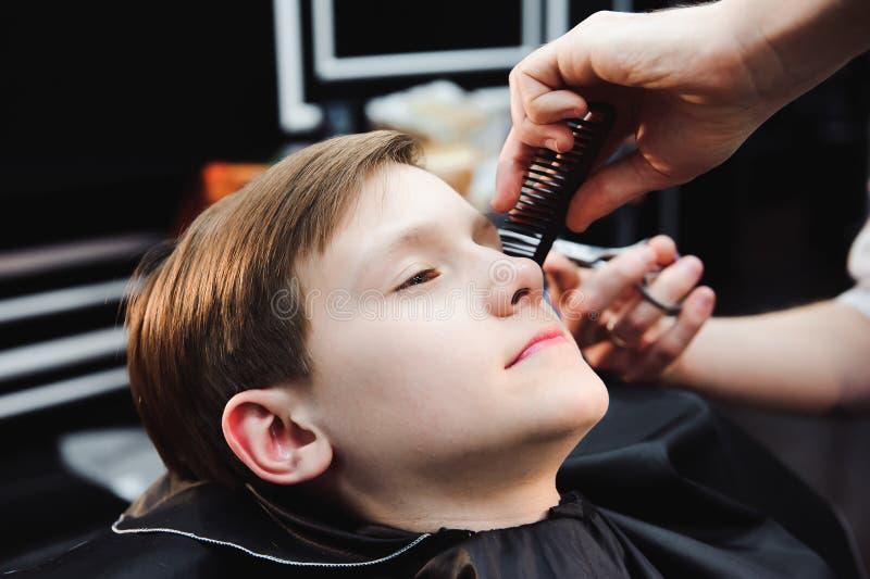 El niño pequeño lindo está consiguiendo corte de pelo del peluquero en la barbería foto de archivo libre de regalías