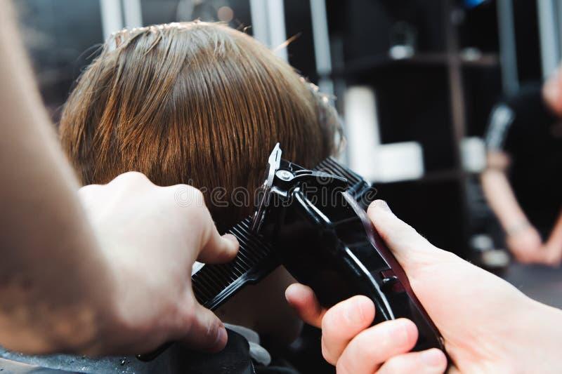 El niño pequeño lindo está consiguiendo corte de pelo del peluquero en la barbería imágenes de archivo libres de regalías