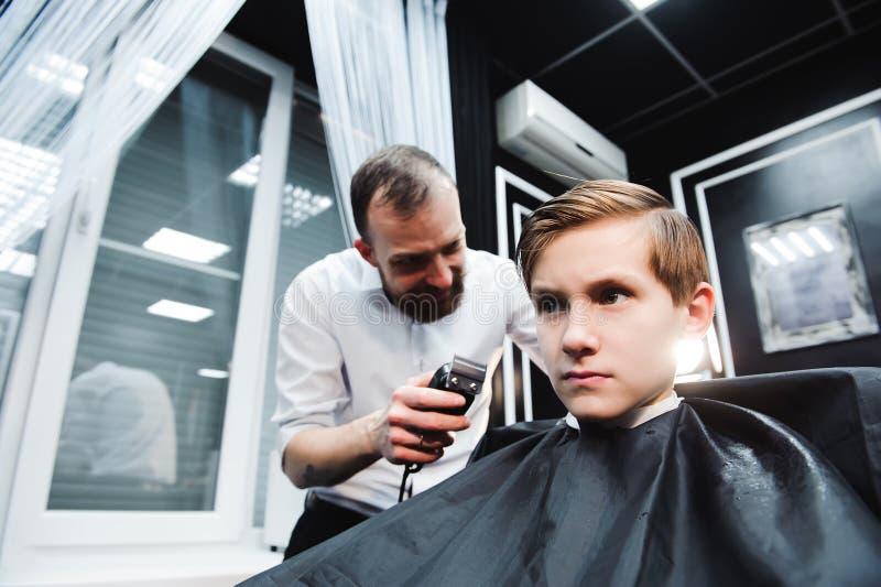 El niño pequeño lindo está consiguiendo corte de pelo del peluquero en la barbería imagen de archivo