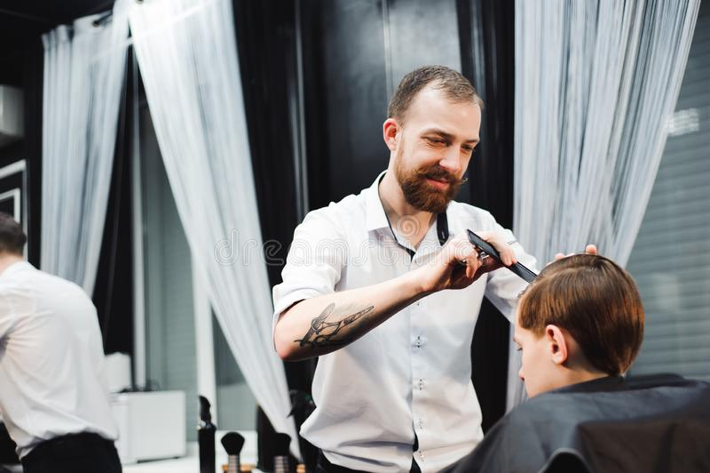 El niño pequeño lindo está consiguiendo corte de pelo del peluquero en la barbería foto de archivo