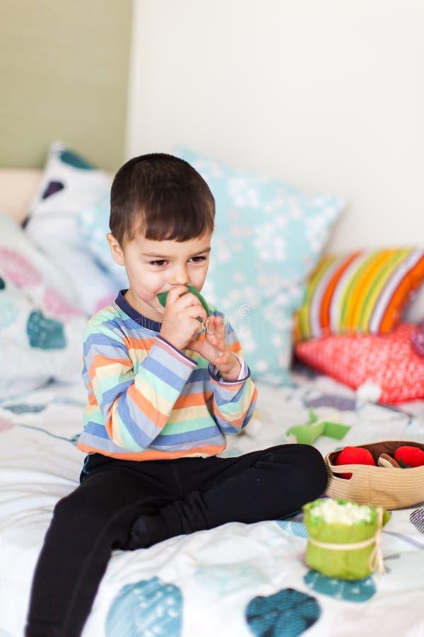 El niño pequeño lindo está jugando con las verduras suaves coloridas que se sientan en cama fotografía de archivo