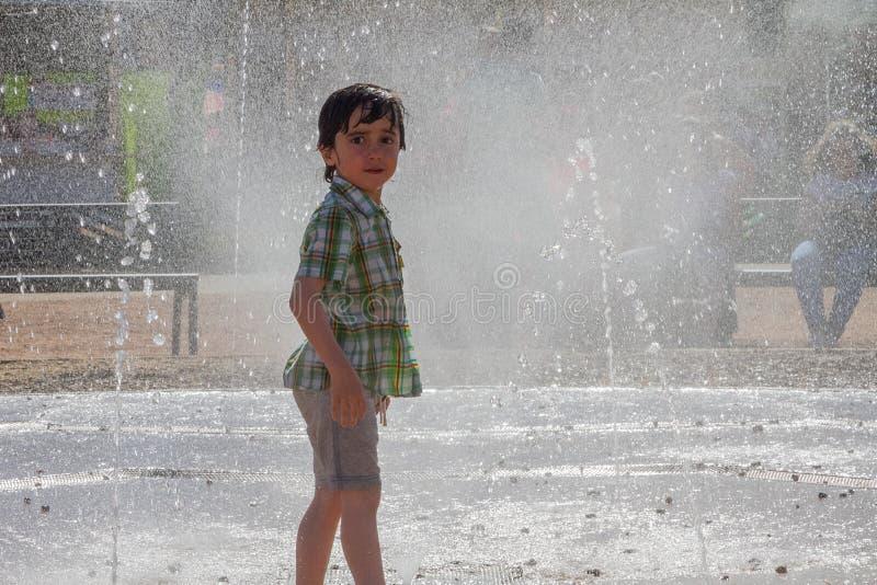 El niño pequeño lindo está riendo y se está divirtiendo que corre debajo de una fuente de agua fotos de archivo