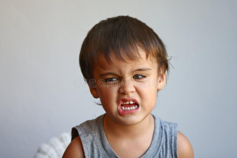 El niño pequeño lindo hace la cara que muestra el eww fotos de archivo