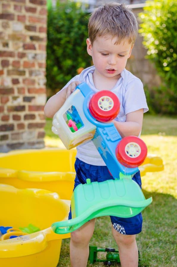 El niño pequeño lindo juega con el coche del juguete en el parque imagenes de archivo