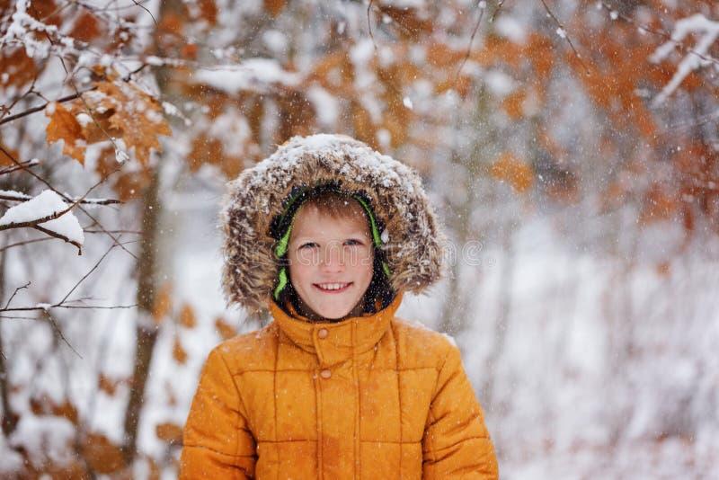 El niño pequeño lindo, niño en invierno viste caminar debajo de la nieve fotos de archivo