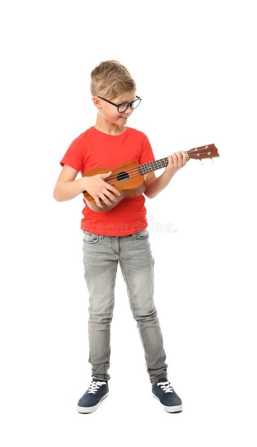 El niño pequeño lindo que tocaba la guitarra aisló fotografía de archivo