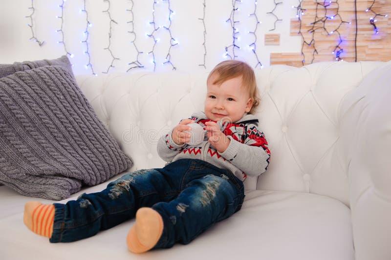El niño pequeño lindo se está sentando en el sofá en casa imagenes de archivo