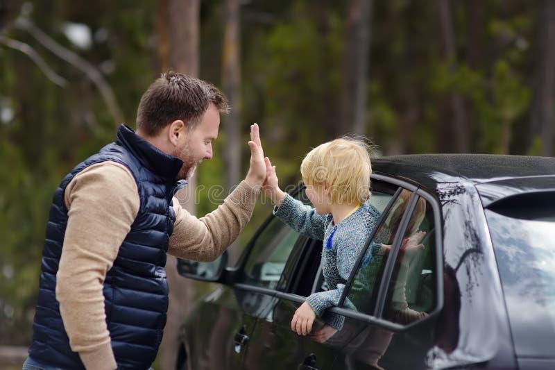 El niño pequeño lindo y su padre está listos para un viaje o un viaje en coche Expresan su placer con un alto-cinco gesto fotos de archivo libres de regalías