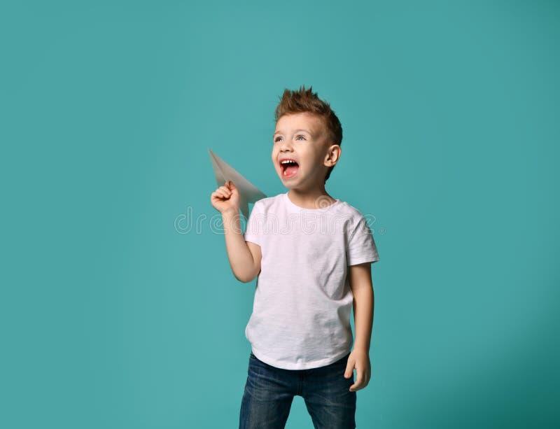 El niño pequeño listo para poner en marcha un avión de papel mira para arriba al cielo y a los gritos superado imágenes de archivo libres de regalías