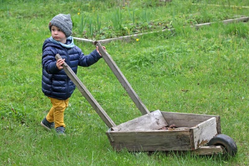 El niño pequeño lleva una carretilla de madera grande en la hierba Niño en el país en la primavera en ropa caliente imágenes de archivo libres de regalías