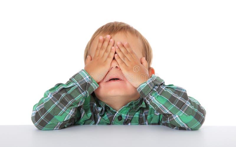El niño pequeño mantiene sus ojos cerrados imagen de archivo libre de regalías