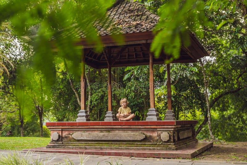 El niño pequeño medita yoga practicante en el balinesse tradicional fotografía de archivo libre de regalías
