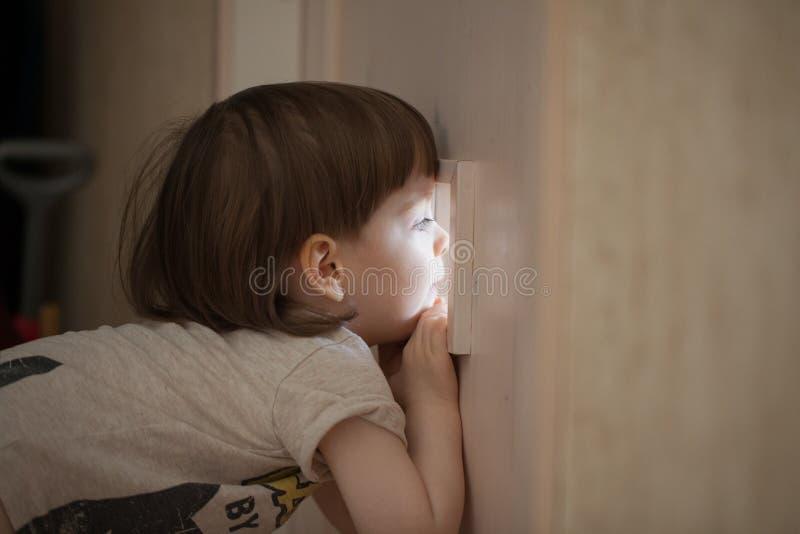El niño pequeño mira en la ventana de la puerta Un niño que espía en sus padres de detrás la puerta cerrada del dormitorio imagen de archivo