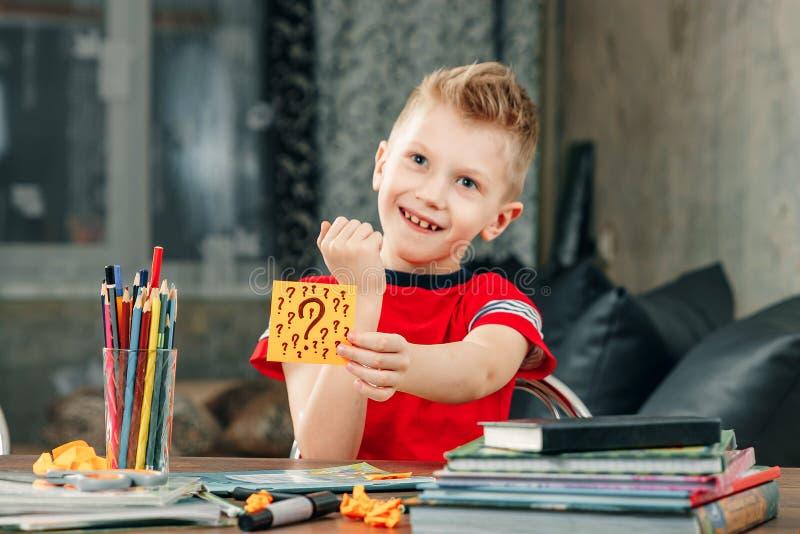 El niño pequeño pensaba, pegando una etiqueta engomada en su frente Soluciona el problema fotografía de archivo libre de regalías