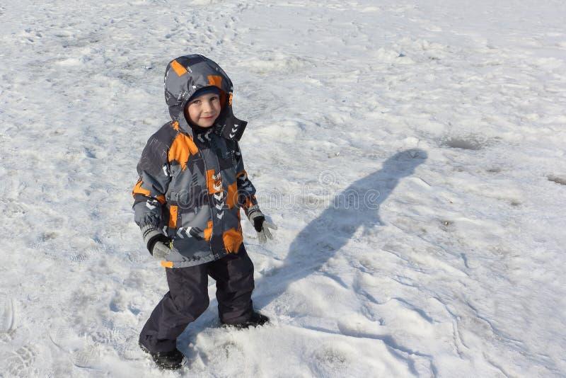 El niño pequeño que camina en nieve foto de archivo