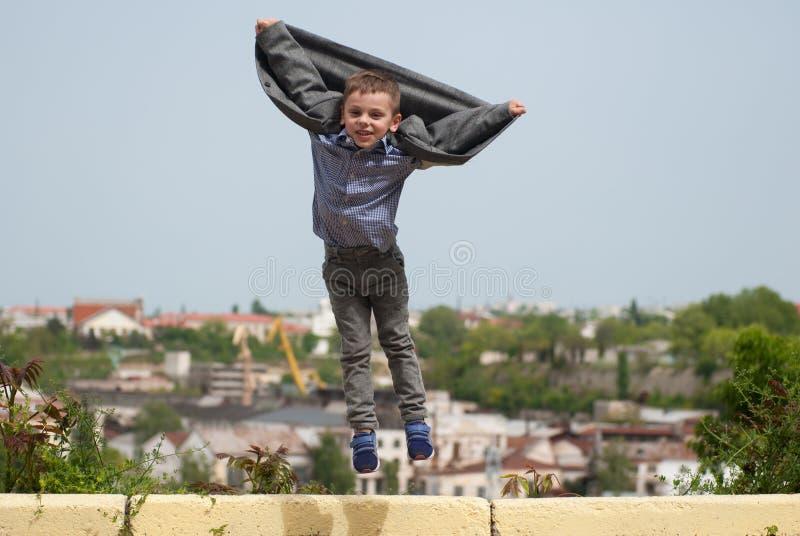 El niño pequeño que salta encima de la chaqueta que revela le gustan las alas fotografía de archivo