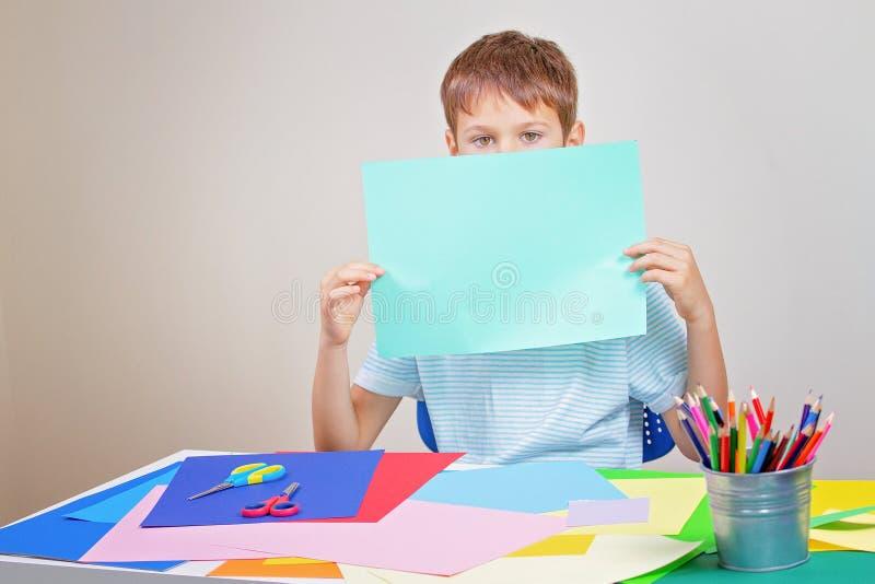 El niño pequeño que se considera en blanco vacia la cara cubierta hoja del papel coloreado imagen de archivo libre de regalías