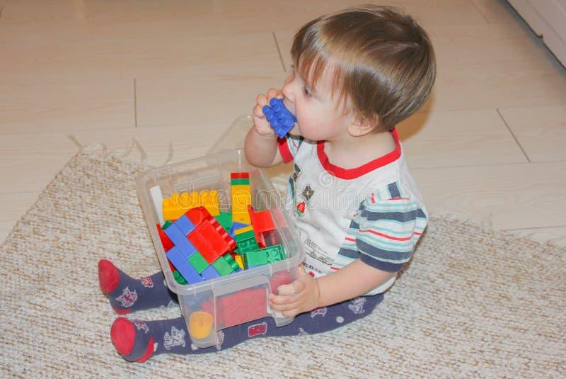 El niño pequeño que se sienta en el piso y las tomas juegan en su boca fotografía de archivo libre de regalías