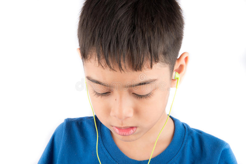 El niño pequeño que sonríe usando las auriculares del auricular escucha la música foto de archivo libre de regalías