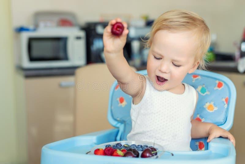 El niño pequeño rubio caucásico lindo adorable goza el probar de diversas bayas orgánicas maduras frescas estacionales que se sie foto de archivo