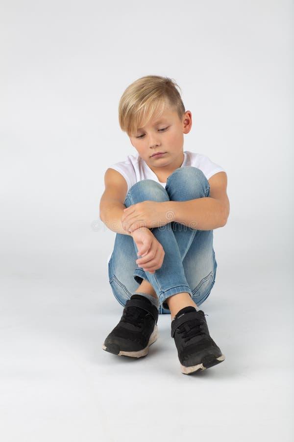 El niño pequeño se está sentando tristemente en el piso imágenes de archivo libres de regalías